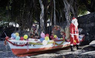 Arrivee d'un pêcheur déguisé en Père Noël pour les enfants de l'école Peverelly à Terre Sainte, à La Réunion, le 10 décembre 2013.