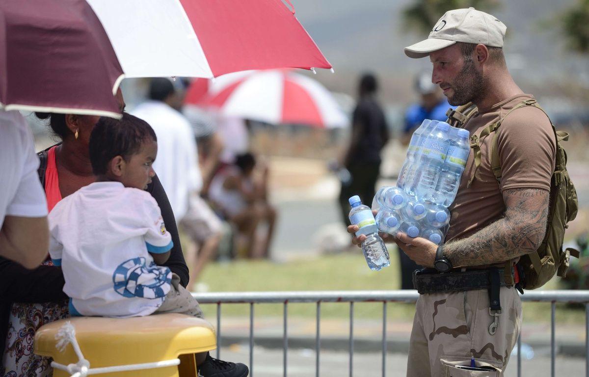 Un militaire néerlandais apporte de l'eau à des enfants sur l'île de Saint-Martin. – Carlos Giusti/AP/SIPA