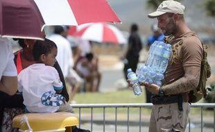 Un militaire néerlandais apporte de l'eau à des enfants sur l'île de Saint-Martin.