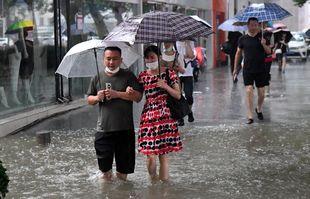 Des gens pataugent sur une route gorgée d'eau à Zhengzhou, capitale de la province chinoise du Henan (centre), le 20 juillet 2021.