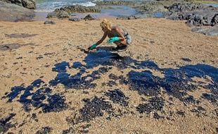 Un bénévole ramasse les galettes d'hydrocarbures à Lauro de Freitas, au Brésil, le 3 novembre 2019.