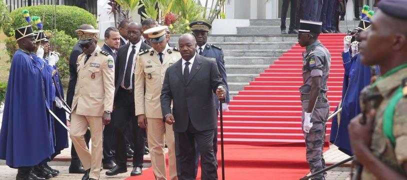 Le président Ali Bongo marche avec une longue canne, lors d'une cérémonie à Libreville, samedi 16 août.