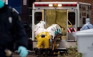 Du personnel de santé en combinaison de protection contre le virus Ebola déchargent le corps d'un médecin infecté, en Sierra Leone, le 15 novembre 2014.
