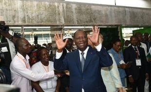 Le président ivoirien Alassane Ouattara salue la foule à son arrivée au bureau de vote, le 25 octobre 2015 à Abidjan, lors de l'élection présidentielle