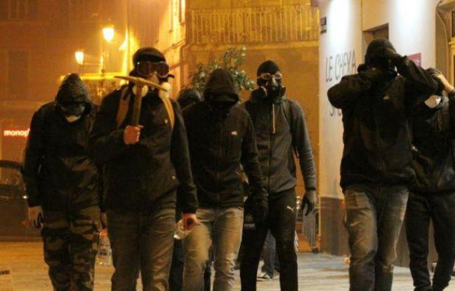 Un groupe d'hommes cagoulés marche le 14 février à Bastia lors d'un rassemblement en soutien à un supporteur du Sporting Club de Bastia blessé à Reims