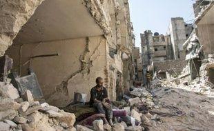 Un homme assis dans les ruines au lendemain d'une frappe aérienne sur le quartier d'al-Mashad à Alep en Syrie, le 17 septembre 2015