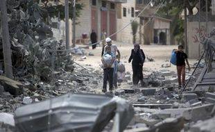 Une famille de réfugiés palestiniens retournent chez eux pour constater ce qu'il reste de leur maison après l'offensive israélienne, le 4 août 2014 près du camp de Rafah dans la bande de Gaza