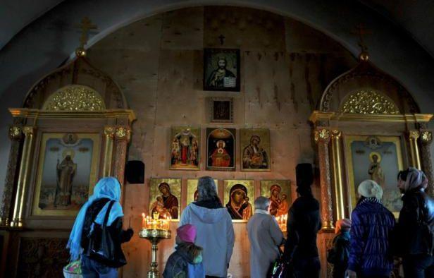 Des Russes prient le 4 mai 2013 dans une église orthodoxe de Saint-Pétersbourg – OLGA MALTSEVA AFP