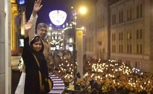 La jeune Pakistanaise Malala Yousafzaï et l'Indien Kailash Satyarthi, prix Nobel de la Paix 2014, saluent la foule depuis le balcon du Grand Hotel où se tient le banquet en l'honneur des lauréats, le 10 décembre 2014 à Stockholm