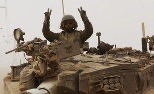 Un soldat israélien à bord de son char Merkava fait le signe de la victoire le 5 août 2014, en rentrant de Gaza