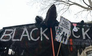 Un manifestant dénonce les actions de BlackRock.
