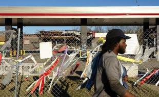 Un homme passe devant la station service dévalisée et incendiée lors d'une émeute au lendemain de la mort de Michael Brown à Ferguson le 16 mars 2015
