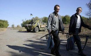 Des habitants de la ville de Gorlivka, dans l'est de l'Ukraine passent, le 18 septembre 2014, devant des militaires loyalistes