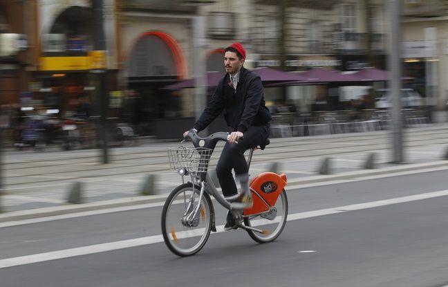 Un cycliste sur un vélo en libre-service cours des 50-Otages à Nantes.