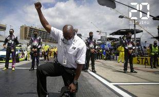 Un officiel de la compétition automobile Nascar, genou  à terre, poing levé durant l'hymne de cette compétition, le 7 juin 2020 à l'Atlanta Motor Speedway à Hampton, en Géorgie, aux Etats-Unis