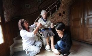(Illustration) Une personne âgée est aidée par une infirmière et une locataire dans son quotidien