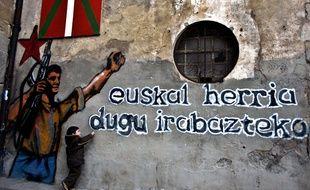 Un enfant joue devant un graffiti à la gloire d'ETA.