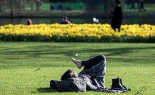 Une femme rpend le soleil dans St James Park à Londres (image d'illustration).