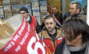 Le député (FN)  Sébastien Chenu (avec son écharpe tricolore) s'est réfugié dans un magasin, lors d'une manifestation, le 15 mars 2018. On le voit à travers la vitre au centre, en haut, de l'image.