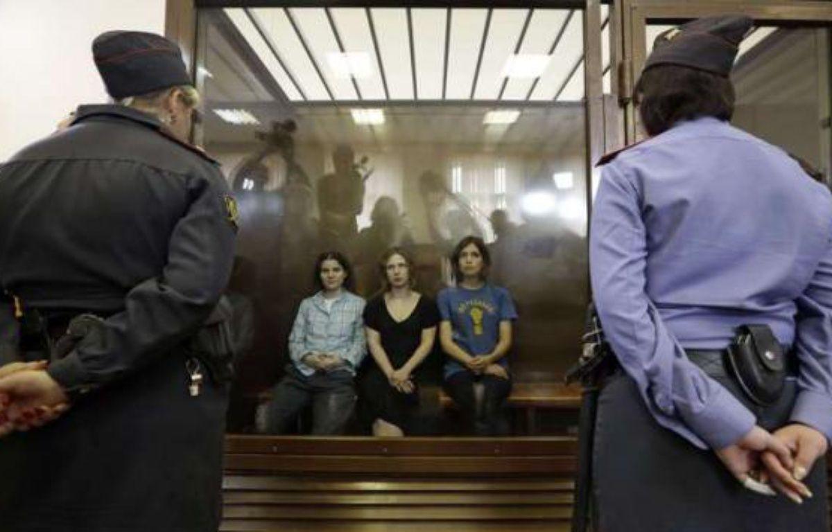 Les trois membres de Pussy Riot sont assises derrière une glasse de verre lors de leur procès, le 17 août 2012 à Moscou. – AP Photo/Sergey Ponomarev