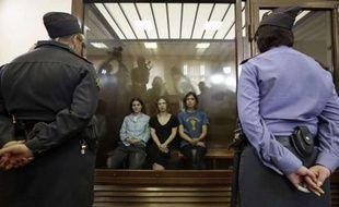 Les trois membres de Pussy Riot sont assises derrière une glasse de verre lors de leur procès, le 17 août 2012 à Moscou.