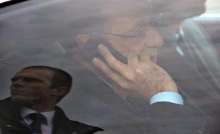 Le président François Hollande au téléphone dans sa voiture lors de sa visite de l'usine Michelin Ladoux à Cebazat près de Clemont-Ferrand, au centre de la France, le 18 avril 2014