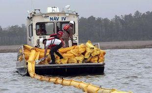 Des marins essaient d'éviter la marée noire et installent des barrages flottants pour tenter de retenir le pétrole qui s'échappe de la plateforme Deepwater, dans le golfe du Mexique.