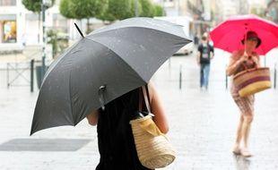 Deux femmes marchent sous la pluie avec un parapluie. Ici le 18 juillet, lors d'un orage à Rennes.