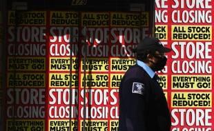 Un homme passe devant des magasins fermés, à New York, le 5 mai 2020.