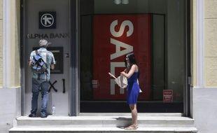 Une femme attend pour retirer de l'argent à un distributeur automatique, le 13 juillet 2015 à Athènes