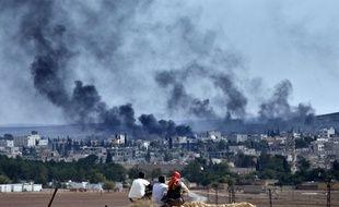 Des réfugiés kurdes regardent la ville de Kobané en proie au chaos, le 26 octobre 2014.