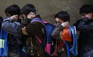 Des enfants se couvrent les oreilles lors d'un exercice d'évacuation dans une école de Douma, bastion des rebelles syriens, organisé par le Croissant rouge syrien le 11 décembre 2014