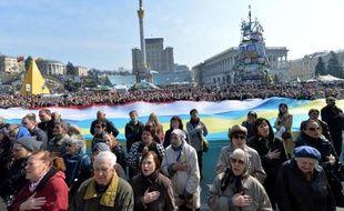 Des manifestants chantent l'hymne ukrainien devant deux drapeaux géants de l'Ukraine et de la Crimée, sur la place de l'Indépendance à Kiev le 23 mars 2014