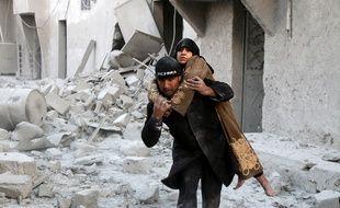 Un sauveteur syrien porte une rescapée d'un bombardement sur un quartier rebelle d'Alep, le 20 novembre 2016.