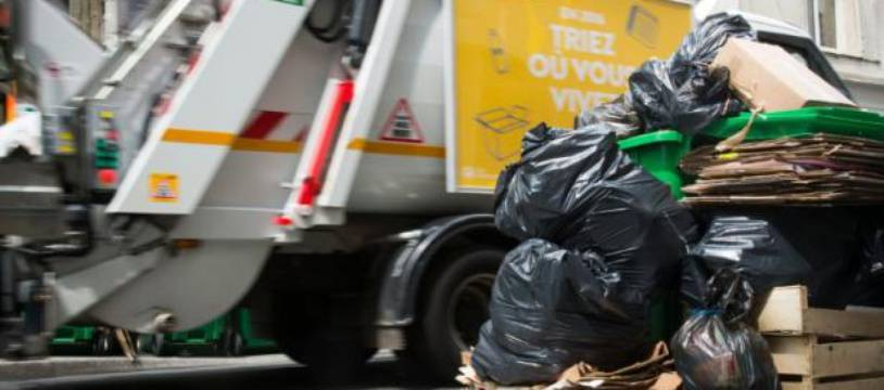 Un camion-poubelle passe à côté de poubelles débordantes de déchets à Paris le 8 juin 2016