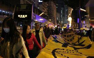 """Une centaine de militants pro-démocratie manifestent dans les rues de Hong Kong portant une bannière de plusieurs mètres qui reprend leur revendication principale: """"Nous voulons un vrai suffrage universel"""", le 24 décembre 2014"""