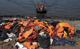 Le 10 septembre 2015, des migrants arrivent sur l'île de Lesbos (Grèce), où ceux qui les ont précédé ont entassé leurs gilets de sauvetage sur la plage après leur traversée. AP Photo/Petros Giannakouris