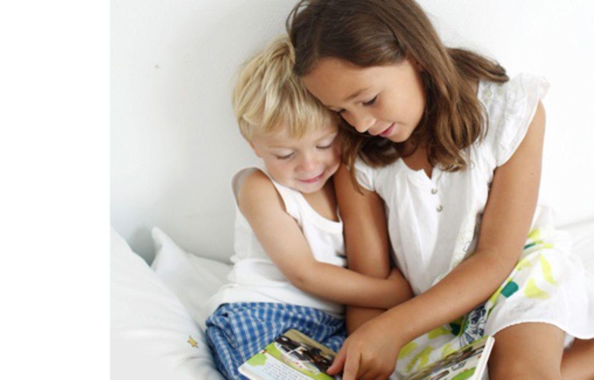 Une petite fille lit un livre a son petit frère, France, mai 2013 – Catherine Delahaye/SIPA