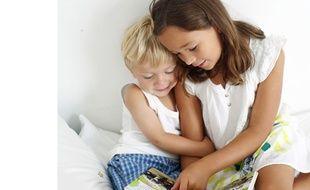 Une petite fille lit un livre a son petit frère, France, mai 2013