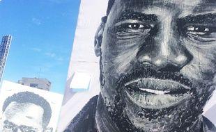 Des portraits de migrants réalisés par Al Sticking ont traversé la ville dimanche.