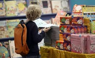 A child looks at a book during the 30th addition of the Salon du Livre et de la Presse Jeunesse (Montreuil Book and Youth Press Fair) one of the leading exhibitions for children and young people in France on November 26, 2014 in Montreuil, northeast of Paris. AFP PHOTO / STEPHANE DE SAKUTIN