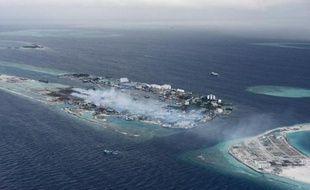 L'approche aérienne des Maldives offre une vue panoramique d'eaux azur et d'îles bordées de coraux mais à l'atterrissage, des volutes de fumée révèlent également un désastre environnemental.