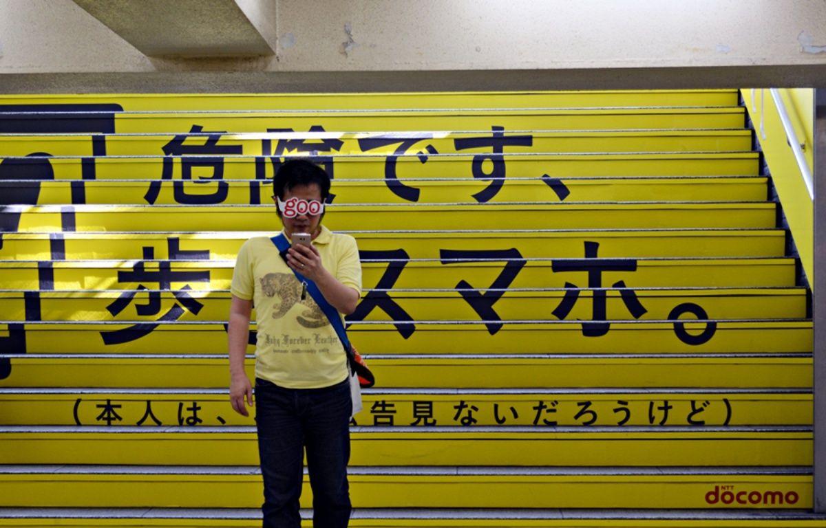 Un homme regarde l'écran de son smartphone, devant un affichage géant avertissant des dangers du smartphone en marchant. – DR