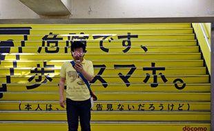 Un homme regarde l'écran de son smartphone, devant un affichage géant avertissant des dangers du smartphone en marchant.