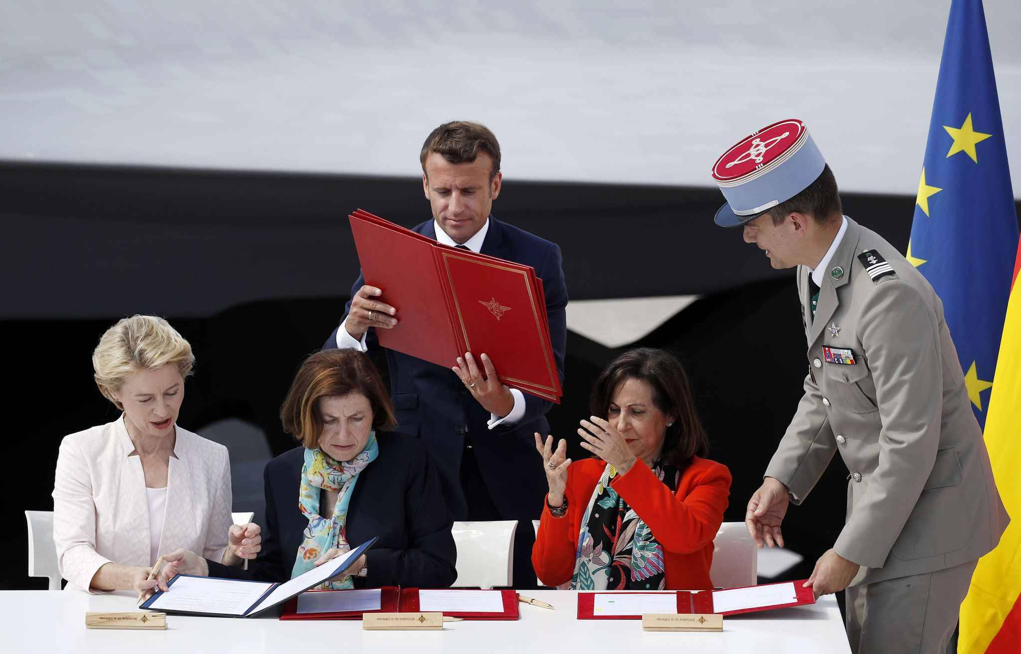 French President Emmanuel Macron, holds documents as German Defense Minister Ursula von der Leyen, left, French Defense Minister Florence Parly and Spanish Defense Minister Margarita Robles, right, attend a signature ceremony as part as the unveiling of the French-German-Spanish new generation fighter model during Le Bourget Airport near Paris, France, Monday June 17, 2019.