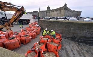 Des employés municipaux installent des sacs de sable devant les fortifications de Saint-Malo, le 19 février 2015, à la veille de marées record