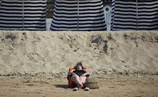 Deauville, le 1er juillet 2015. Une femme bronze sur la plage.