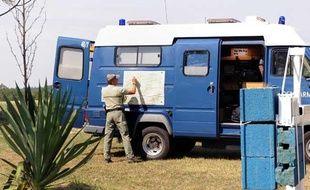 Un gendarme consulte une carte fixée sur une voiture de gendarmerie stationnée en bordure de la forêt de Othe, le 9 septembre 2009 près de la commune de Joigny où se déroulent les recherches pour retrouver Jean-Pierre Treiber.