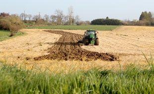 Illustration d'un tracteur travaillant dans un champ agricole près de Rennes.