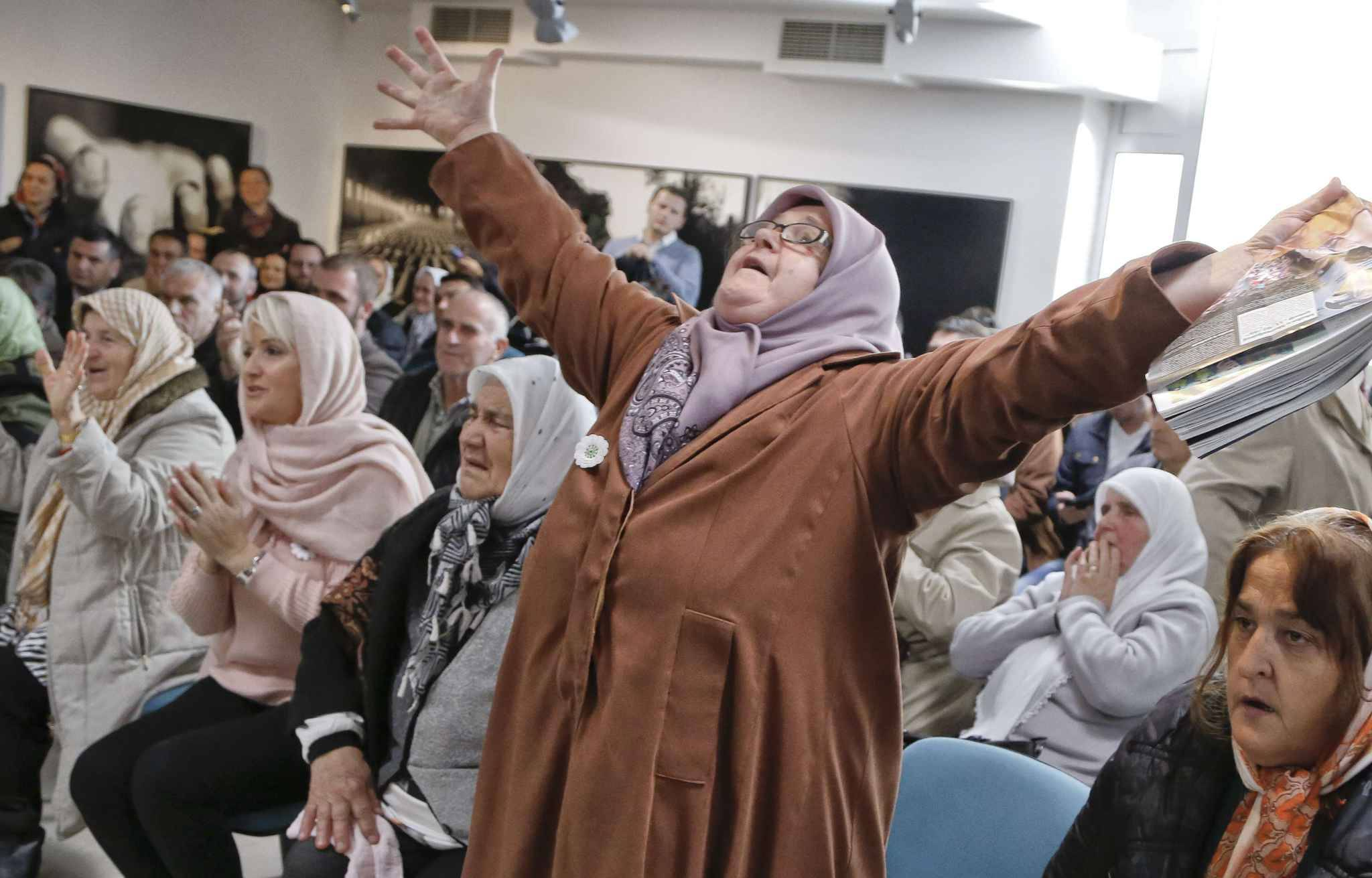 Ediba Salihovic, right, stands up and raises her hands as she reacts along with other Bosnian women upon hearing the sentence at the end of former Bosnian Serb military chief Gen. Ratko Mladic's trial at the memorial center in Potocari, near Srebrenica, Bosnia, Wednesday, Nov. 22, 2017. A U.N. court has convicted former Bosnian Serb military chief Gen. Ratko Mladic of genocide and crimes against humanity and sentenced him to life in prison for atrocities perpetrated during Bosnia's 1992-1995 war.